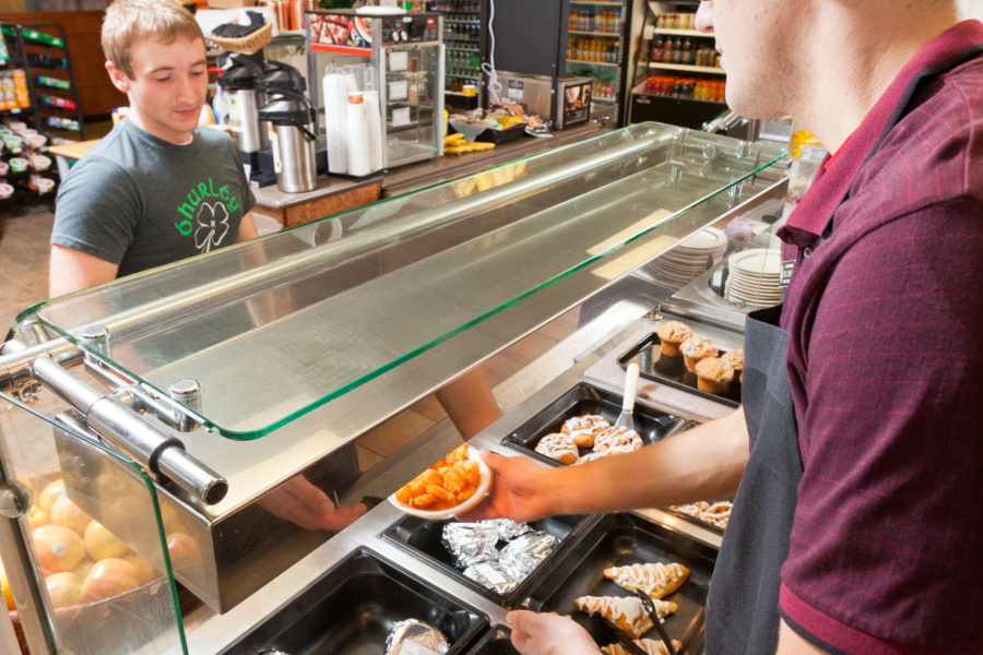 Student dining worker serves food at Newell's Deli