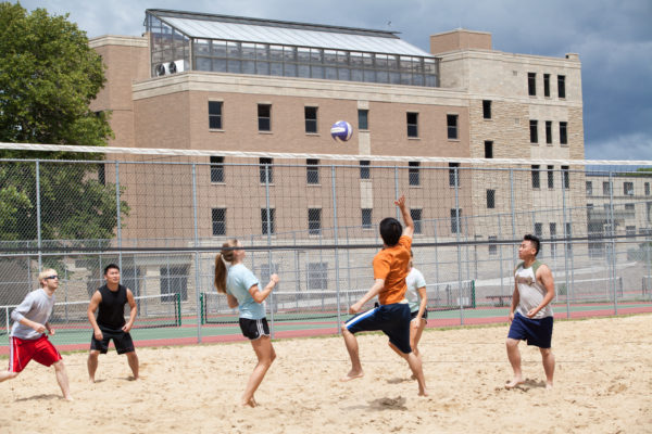 Group of people plays volleyball outside Lakeshore residence halls