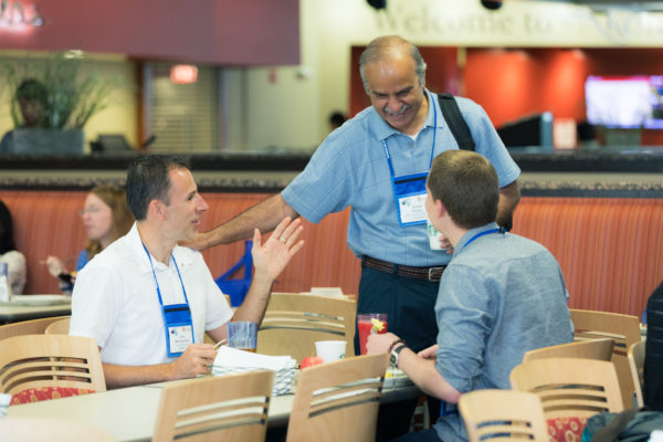Conference attendees greet each other at breakfast