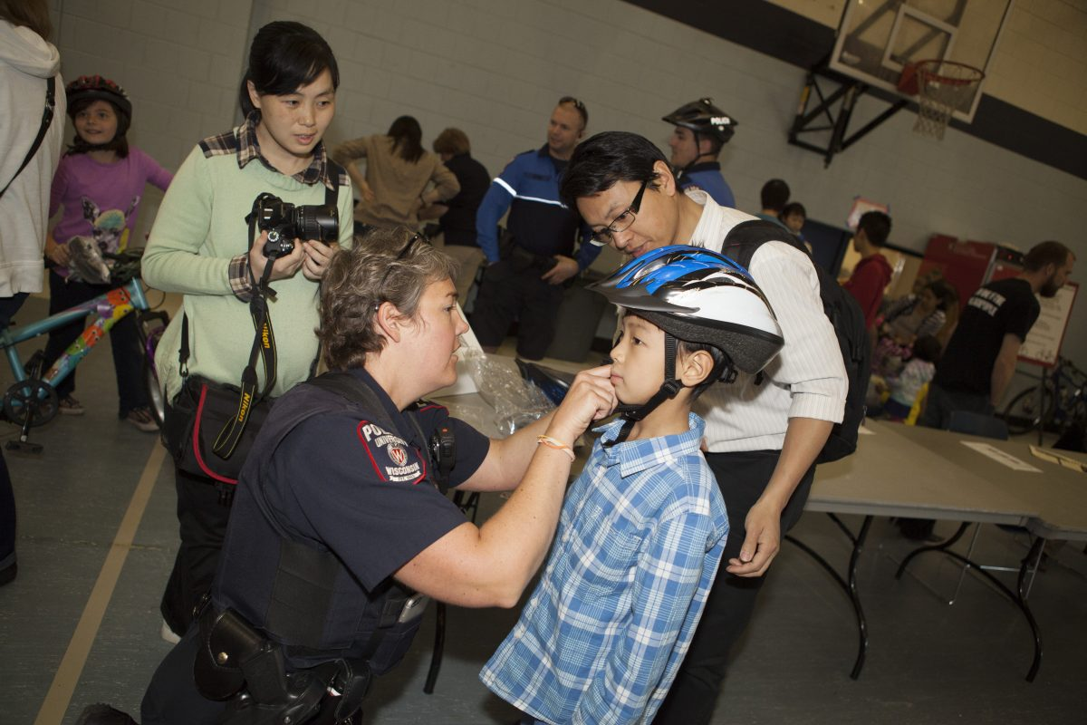 A UWPD Officer fits a bike helmet for a young man.
