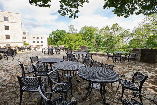 empty tables outside Waters Hall in the summer