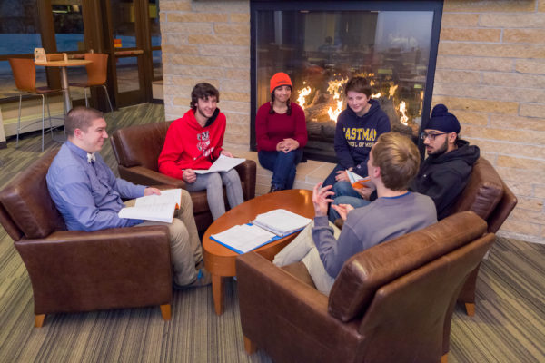 Open House residents spend time together in front of the fireplace in Dejope Hall