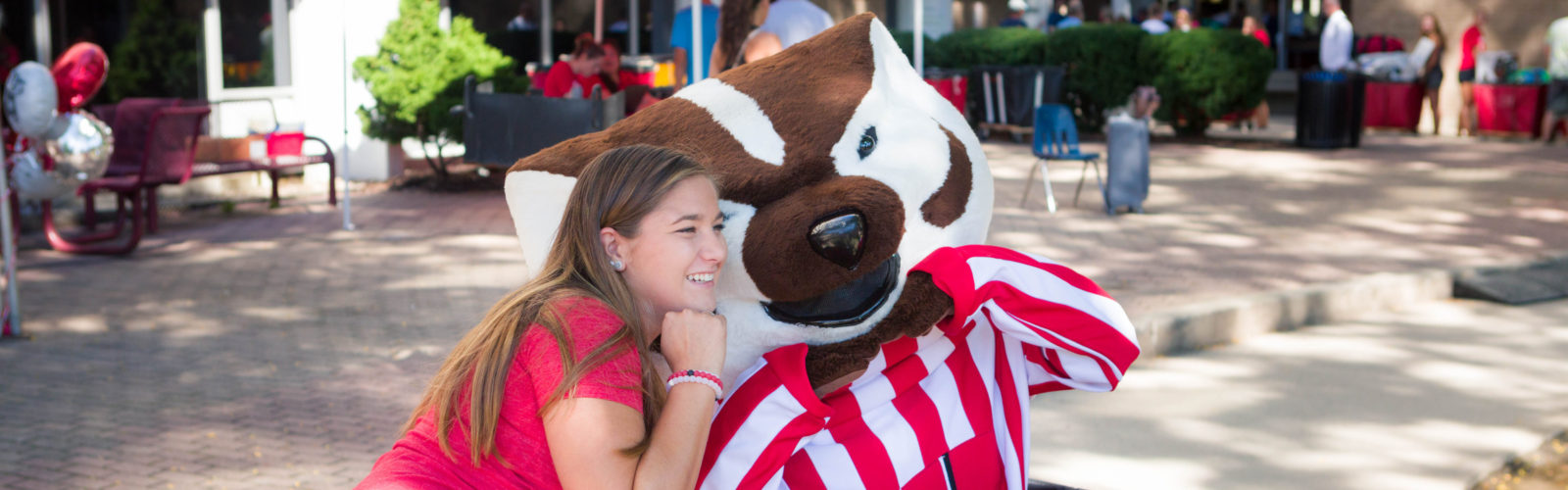 A student poses for a photo with Bucky Badger during move-in at Witte Residence Hall