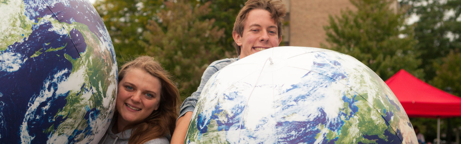 two students pose with giant inflatable earths for Sustain-a-Bash