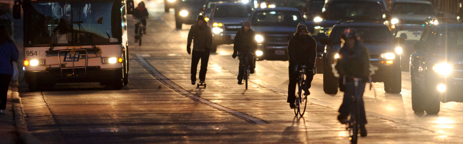 A skateboarder joins bicyclists pedaling in the bike lane along University Avenue against a backdrop of car lights and rush hour-traffic