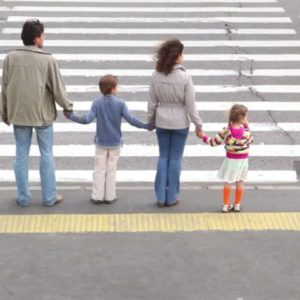 Family standing at crosswalk
