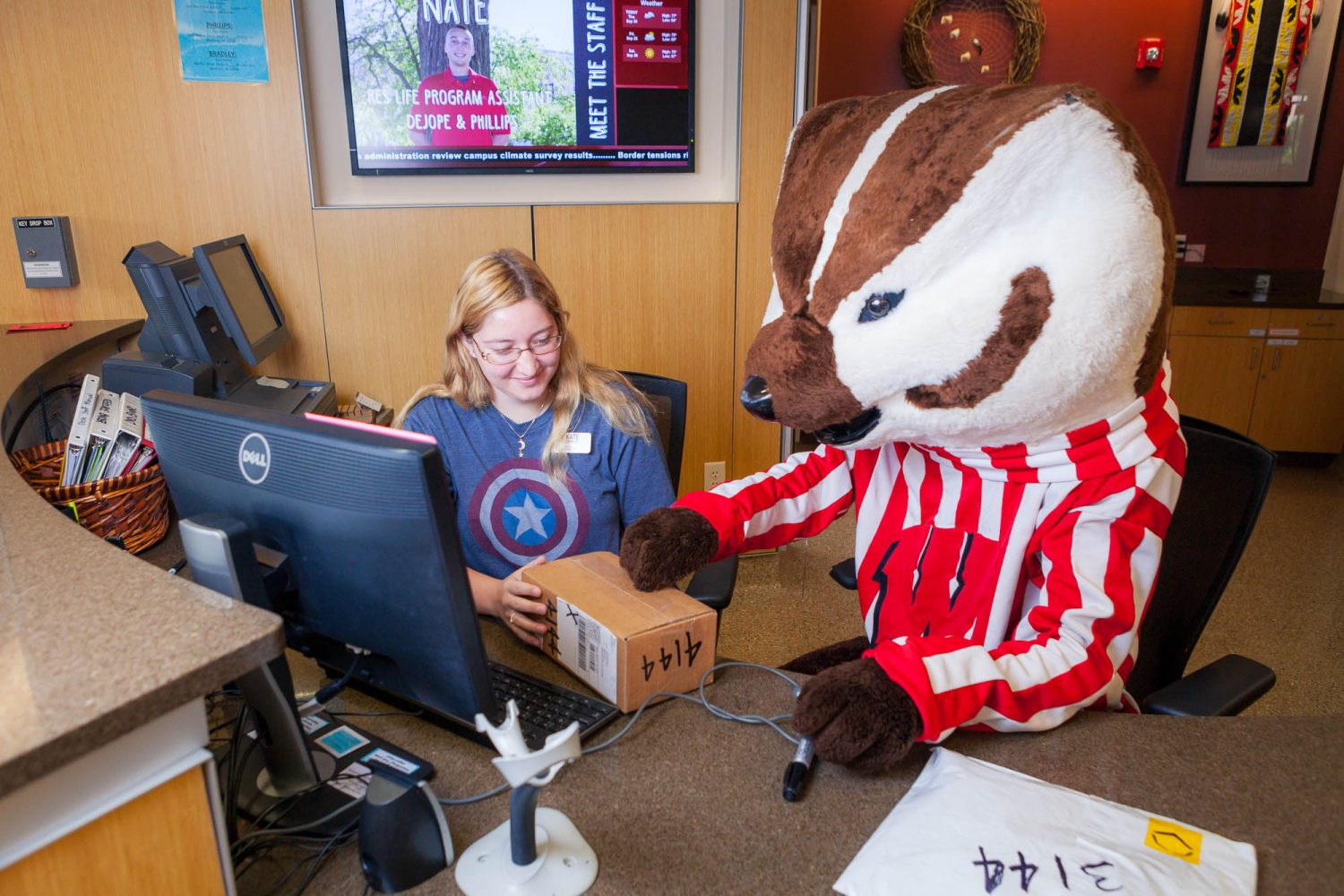 Bucky assisting a hall desk staff with checking-in a package