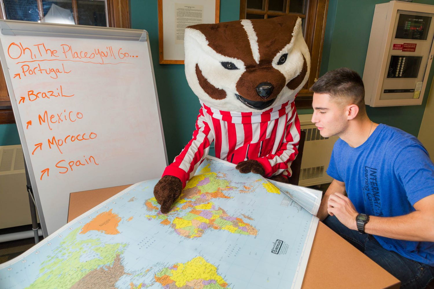 Bucky with a student pointing at a world map