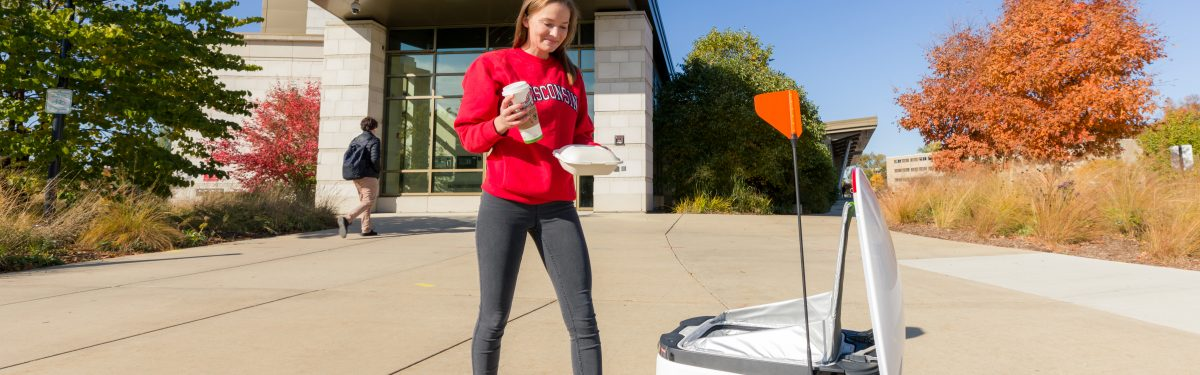 A student outside Dejope Residence Hall receives a delivery from a Starship Delivery robot. Photo by Joel Ninmann, University Housing.