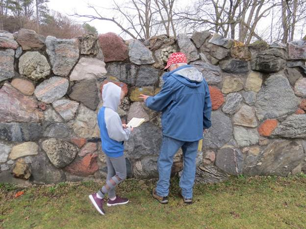 Emeritus Professor David Mickelson talks with a young visitor about the stones in the rock wall. Photo by Gisela Kutzbach.