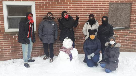 A group of residents from Harvey Street Apartments pose around a snowman.