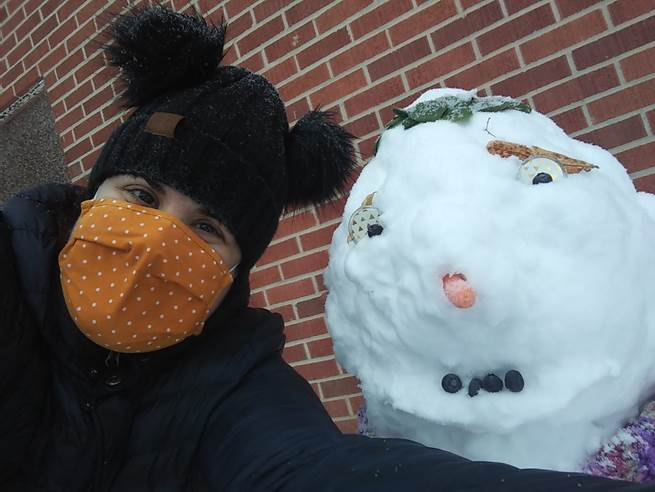A Harvey Street resident poses with a snowman they built.