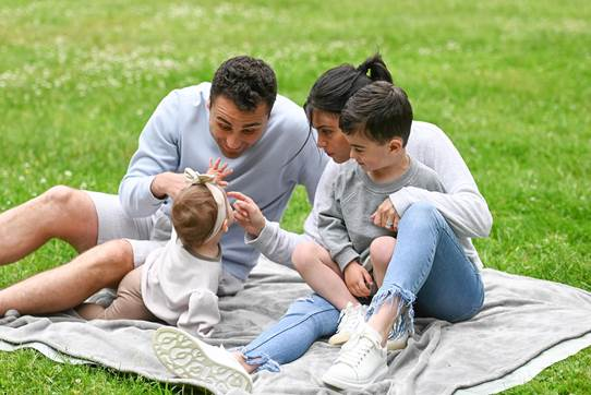 Family cuddling on a blanket in the park