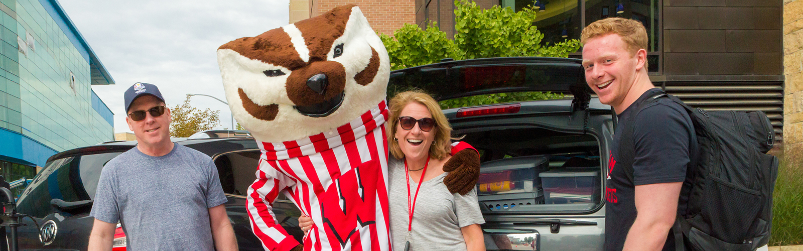 A student and his parents with Bucky Badger at move-in