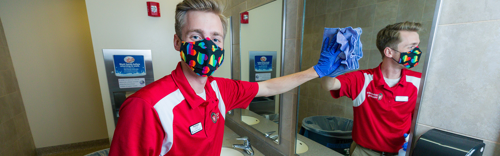 Facilities student employee cleaning a restroom