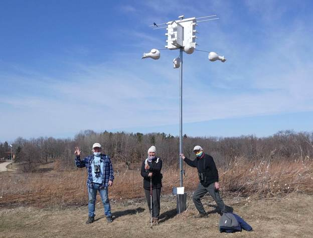Volunteers pose for a photo after preparing the Purple Martin house for the birds' spring return. You can see an Eagle Heights Apartment in the background. Photo by David Liebl.